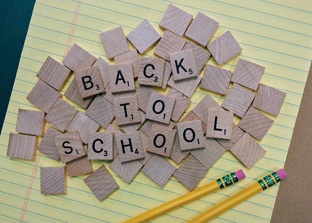 "Brown Scrabble Tiles on Yellow Paper with Two Pencils. The letters are reading: ""Back to School"""