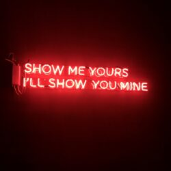 "a neon sign saying: ""Show me yours, I'll show you mine"""